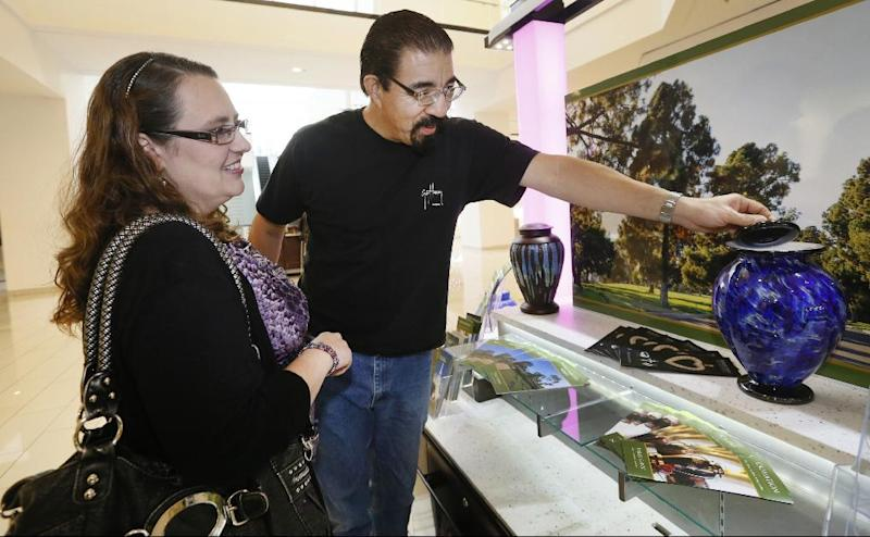 In this photo taken Thursday, Jan. 30, 2014, Mark Sanchez and his wife Lea' Anne Sanchez look at a Dodger's theme cremation urn at the Forest Lawn stand at the Glendale Galleria mall in Glendale, Calif. Forest Lawn, famous as the final resting place for everyone from Al Jolson to Michael Jackson, has begun staffing outlets at shopping malls, reasoning that planning for death, either for a loved one or yourself, might not be quite as intimidating for some people if it takes place in a lively, happy place like a mall rather than the more somber confines of a cremation home. (AP Photo/Damian Dovarganes)