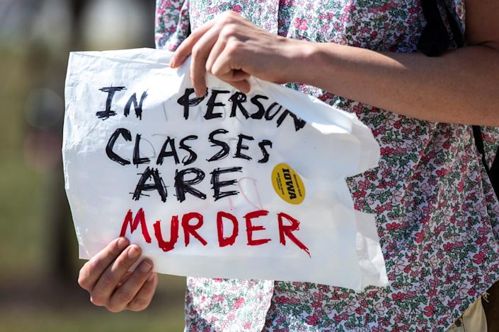 A person holds a sign,