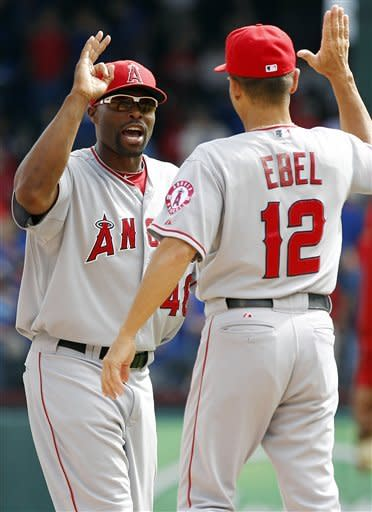 Los Angeles Angels right fielder Torii Hunter (48) celebrates their 5-4 win over the Texas Rangers with third base coach Dino Ebel (12) after the final out of the first baseball game of a doubleheader, Sunday, Sept. 30, 2012, in Arlington, Texas. (AP Photo/LM Otero)