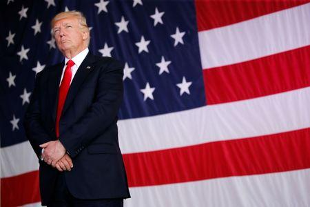 U.S. President Trump stands in front of a U.S. flag while listening to U.S. first lady Melania Trump give a speech to U.S. troops at the Naval Air Station Sigonella before returning to Washington D.C. at Sigonella Air Force Base in Sigonella