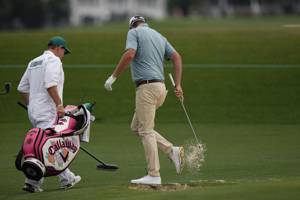 Marc Leishman, of Australia, knocks the sand off his shoe after hitting out of a bunker on the second hole during the second round of the Masters golf tournament on Friday, April 9, 2021, in Augusta, Ga. (AP Photo/Matt Slocum)