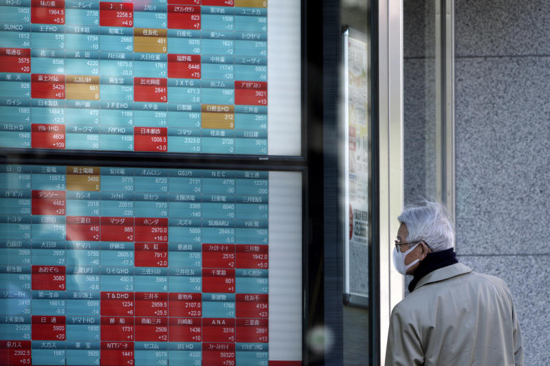 A man looks at an electronic stock board showing Japan's Nikkei 225 index at a securities firm in Tokyo Tuesday, Feb. 18, 2020. Shares have fallen in Asia as the impact from the virus outbreak that began in China deepened, with Apple saying it would fail to meet its profit target and China moving to cancel major events including the Beijing auto show. (AP Photo/Eugene Hoshiko)