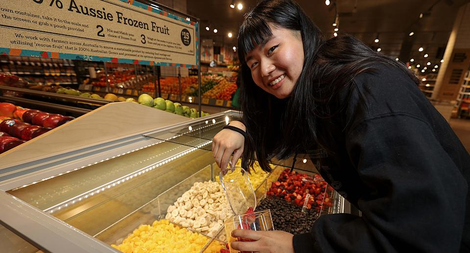 A woman puts frozen fruit into a container.