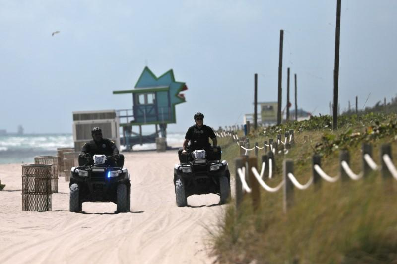 Police officers patrol the beach after local authorities order the closing of all the beaches in Miami-Dade county for precaution due to coronavirus disease (COVID-19) spread, in Miami Beach