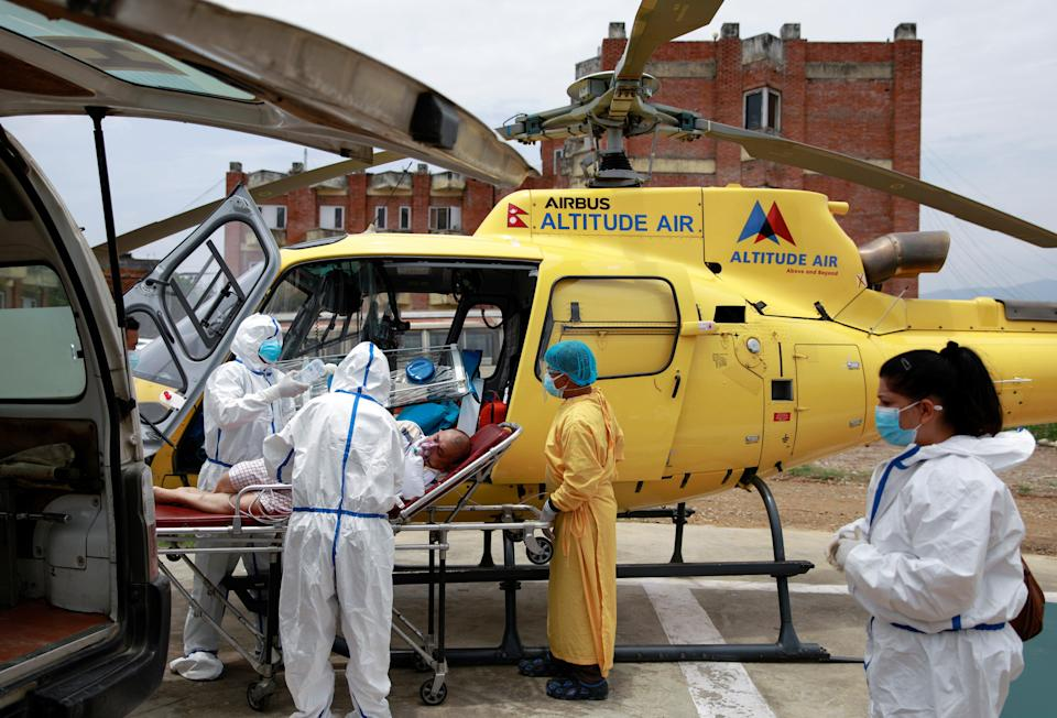 <p>Health workers in Kathmandu carry a Covid patient from a helicopter to an ambulance after being airlifted due to health complications</p> (REUTERS)