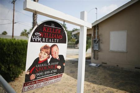 A real estate sign is seen outside a deserted home stripped of its copper wiring in San Bernardino