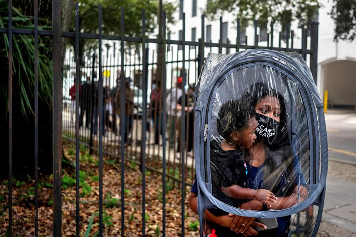 Dana Clark and her 18-month-old son Mason wait in line at City Hall as early voting begins for the upcoming presidential election in New Orleans, Louisiana, U.S., October 16, 2020. Clark said she donned this protective cover because she didn't know how many people would be wearing masks in line, and her child doesn't have a mask. She said she works as a teacher, and wanted to take precautions for her students' sakes.