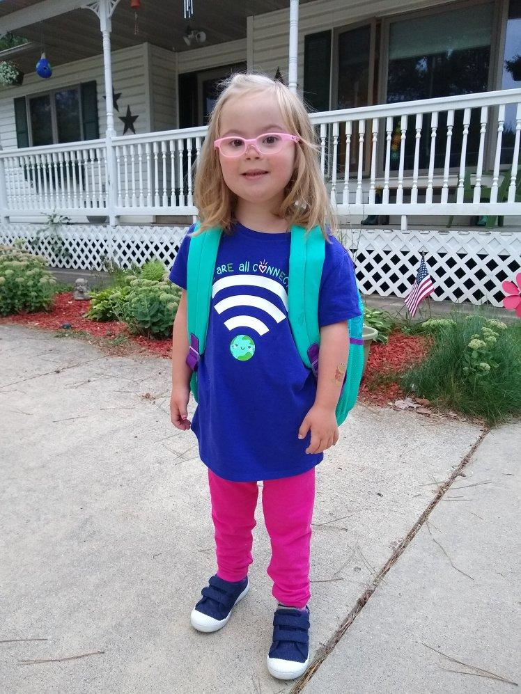 Willow in her pink glasses and backpack ready for school.