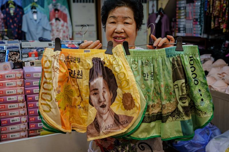Shin Soon-nam displays shorts decorated with images from South Korean currency.