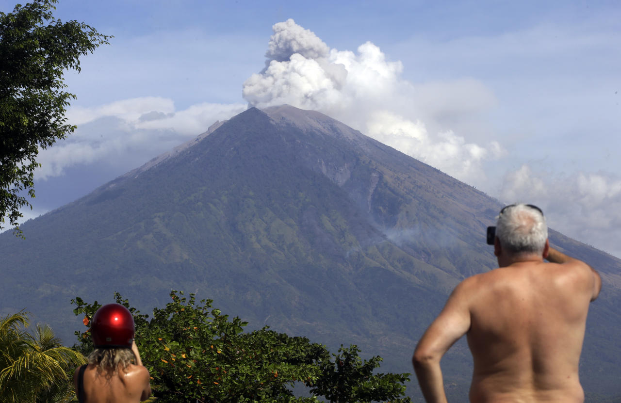 Tourists watch Mount Agung erupt in Karangasem, Bali, Indonesia, Tuesday, July 3, 2018. The volcano on the Indonesian tourist island of Bali erupted Monday evening, ejecting a 2,000-meter-high (6,560-foot-high) column of thick ash and hurling lava down its slopes. (AP Photo/Firdia Lisnawati)