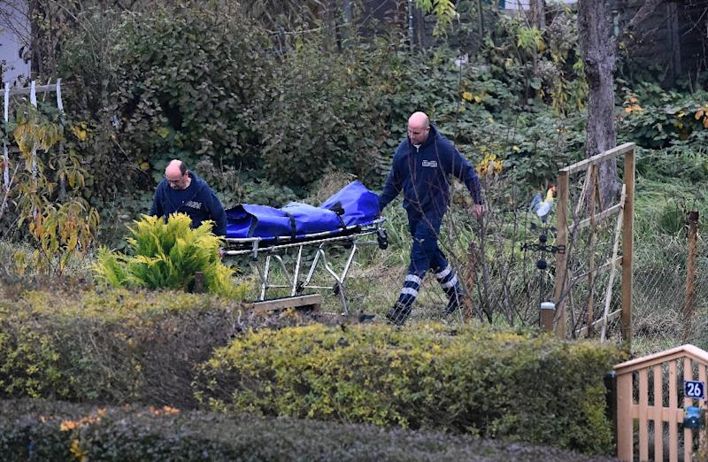 "Forensic doctors push a stretcher through the garden allotment ""Am Eckbusch"" in Luckenwalde, south of Berlin, on October 30, 2015 (AFP Photo/Tobias Schwarz)"