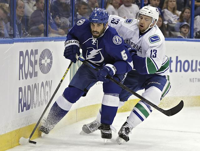 Tampa Bay Lightning defenseman Jason Garrison (5) beats Vancouver Canucks center Nick Bonino (13) to a loose puck behind the goal during the first period of an NHL hockey game Tuesday, Jan. 20, 2015, in Tampa, Fla. (AP Photo/Chris O'Meara)