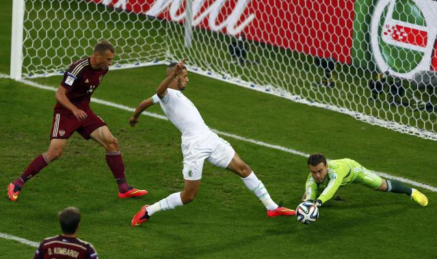 Russia's goalkeeper Igor Akinfeev (R) saves the ball from Algeria's Islam Slimani (C) during their 2014 World Cup Group H soccer match at the Baixada arena in Curitiba June 26, 2014. REUTERS/Amr Abdallah Dalsh (BRAZIL - Tags: SOCCER SPORT WORLD CUP)