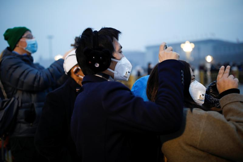 People wearing face masks use their cellphones at the Tiananmen Square, as the country is hit by an outbreak of the new coronavirus, in Beijing, China January 27, 2020. REUTERS/Carlos Garcia Rawlins