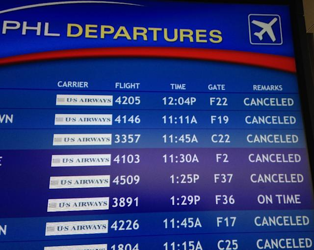 The departure board at the Philadelphia International Airport shows canceled flights on Monday, Feb. 3, 2014. A storm has already dropped snow in the area and could bring up to 8 inches to Philadelphia and New York, along with temperatures in the 30s, according to the National Weather Service. Parts of Maryland and West Virginia were expecting up to 10 inches. (AP Photo/Karen Testa)