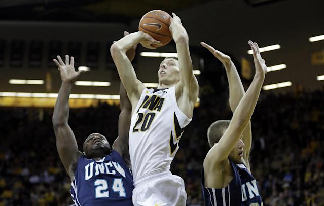 Iowa forward Jarrod Uthoff, center, drives to the basket between UNC-Wilmington's Addison Spruill, left, and Dylan Sherwood during the first half of an NCAA college basketball game, Friday, Nov. 8, 2013, in Iowa City, Iowa. (AP Photo/Charlie Neibergall)