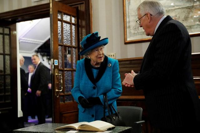 The Queen signs the visitors' book during a visit to the new headquarters of the Royal Philatelic Society in London