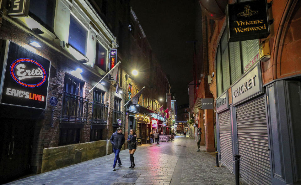 An empty looking Mathew Street in Liverpool, England, as drinkers stay at home and follow coronavirus restrictions, Friday, Oct. 9, 2020, ahead of a new three-tiered system of restrictions that Prime Minister Boris Johnson will outline on Monday that is expected to cause pubs and restaurants to shut across the north of England. (Peter Byrne/PA via AP)