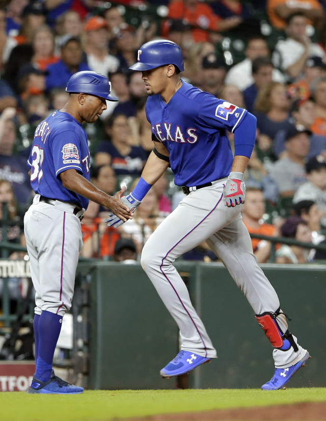 Texas Rangers third base coach Tony Beasley, left, congratulates Ronald Guzman, right, as he rounds third base on his home run during the eighth inning of a baseball game against the Houston Astros on Wednesday, Sept. 18, 2019, in Houston. (AP Photo/Michael Wyke)