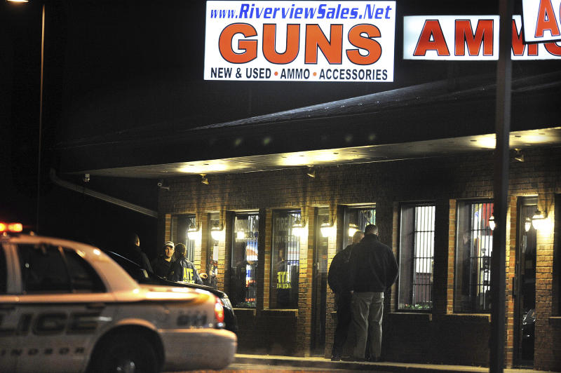 In this Dec. 20, 2012 photo, law enforcement officials stand outside Riverview Gun Sales, as authorities raid the store in East Windsor, Conn.  The shop, which sold a gun to Nancy Lanza, mother of Newtown school shooter Adam Lanza, had its federal firearms license revoked by the Bureau of Alcohol, Tobacco, Firearms and Explosives, which confirmed the revocation Thursday, April 4, 2013. (AP Photo/Jessica Hill)