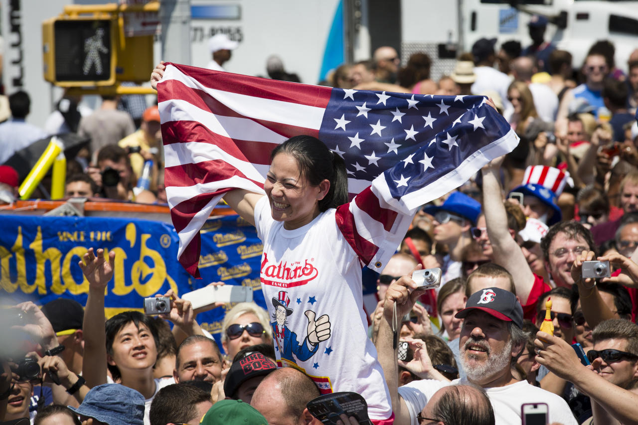 "Sonya ""The Black Widow"" Thomas is carried through the crowds after breaking her world record during the Nathan's Famous Women's Hot Dog Eating World Championship, Wednesday, July 4, 2012, at Coney Island, in the Brooklyn borough of New York. Thomas won her second consecutive women's competition with 45 downed hot dogs. (AP Photo/John Minchillo)"