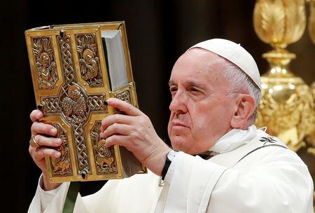 Pope Francis holds the Bible as he leads the Easter vigil Mass in Saint Peter's Basilica at the Vatican, April 20,2019. REUTERS/Remo Casilli