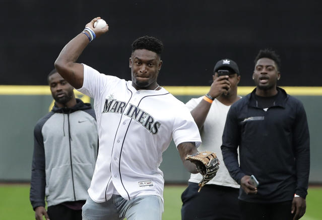Seattle Seahawks rookie wide receiver DK Metcalf throws out the first pitch at a baseball game between the Seattle Mariners and the Baltimore Orioles, as other rookies from the NFL football team look on, Thursday, June 20, 2019, in Seattle. (AP Photo/Ted S. Warren)