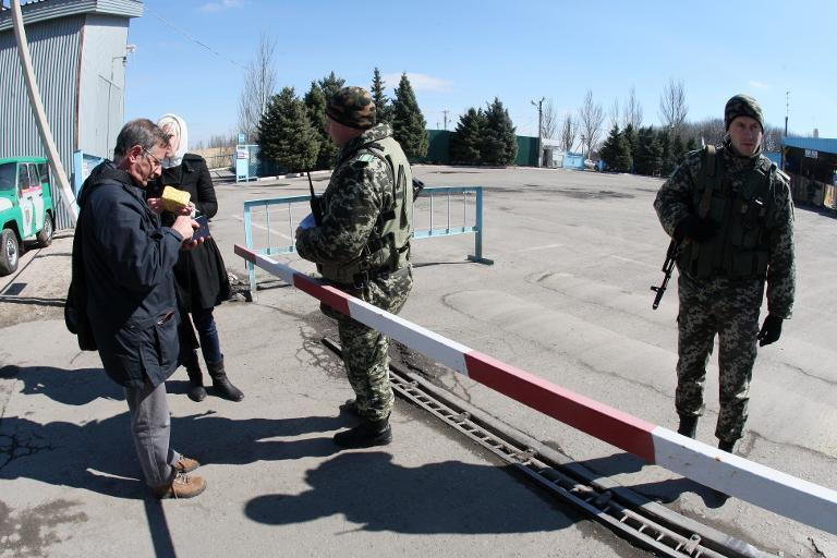 Ukrainian border guard checks a passport at the Uspenka check point on the border between Ukraine and Russia, some 120 km from the eastern city of Donetsk on March 21, 2014