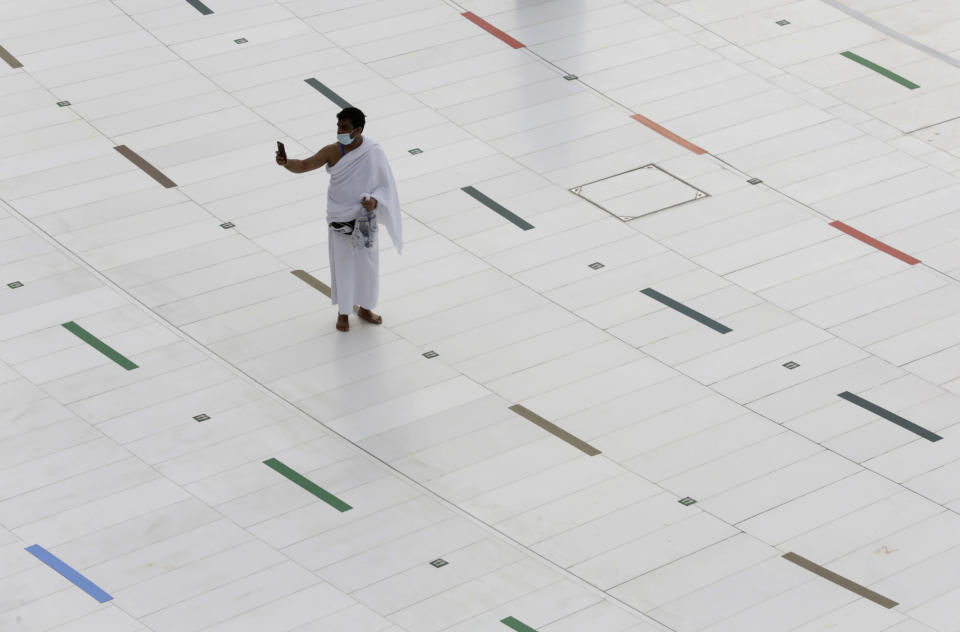 A Muslim pilgrim takes a selfie at the Grand Mosque, as he wears a mask and stands on social distancing signs, a day before the annual hajj pilgrimage, Saturday, July 17, 2021. The pilgrimage to Mecca required once in a lifetime of every Muslim who can afford it and is physically able to make it, used to draw more than 2 million people. But for a second straight year it has been curtailed due to the coronavirus with only vaccinated people in Saudi Arabia able to participate. (AP Photo/Amr Nabil)