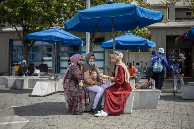 A group of friends are pictured eating ice cream on Granville Island in Vancouver, British Columbia on Friday June 18, 2021. (Ben Nelms/CBC - image credit)