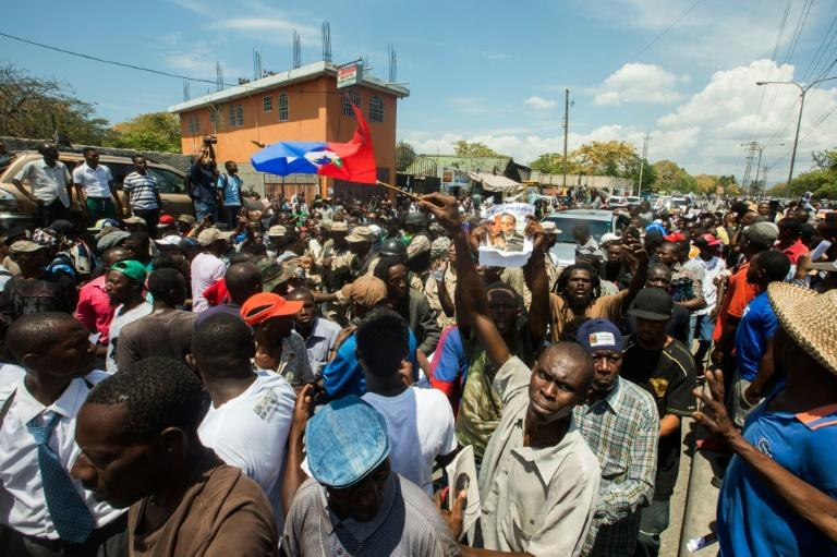Crowds gather around the car of former Haitian President Jean-Bertrand Aristide, as he makes a rare public appearance to testify as a witness in a money laundering case