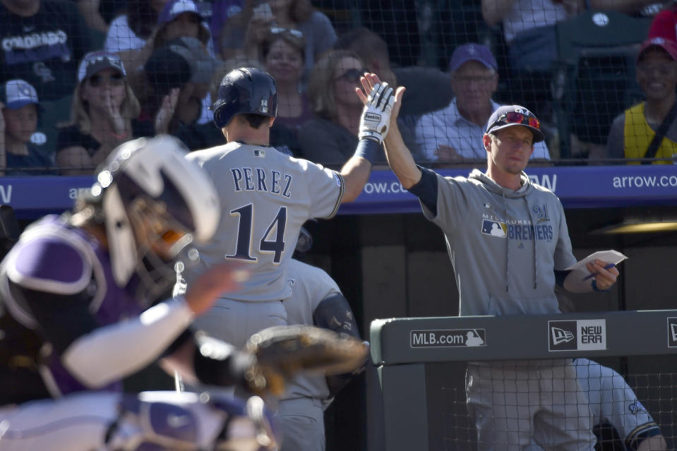 Milwaukee Brewers third baseman Hernan Perez (14) high-fives manager Craig Counsell (30) after hitting a home run in the sixth inning of a baseball game against the Colorado Rockies, Sunday, Sept. 29, 2019, in Denver. (AP Photo/John Leyba)