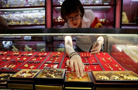 A sales assistant takes out gold ornaments for a customer at Caibai Jewelry store in Beijing
