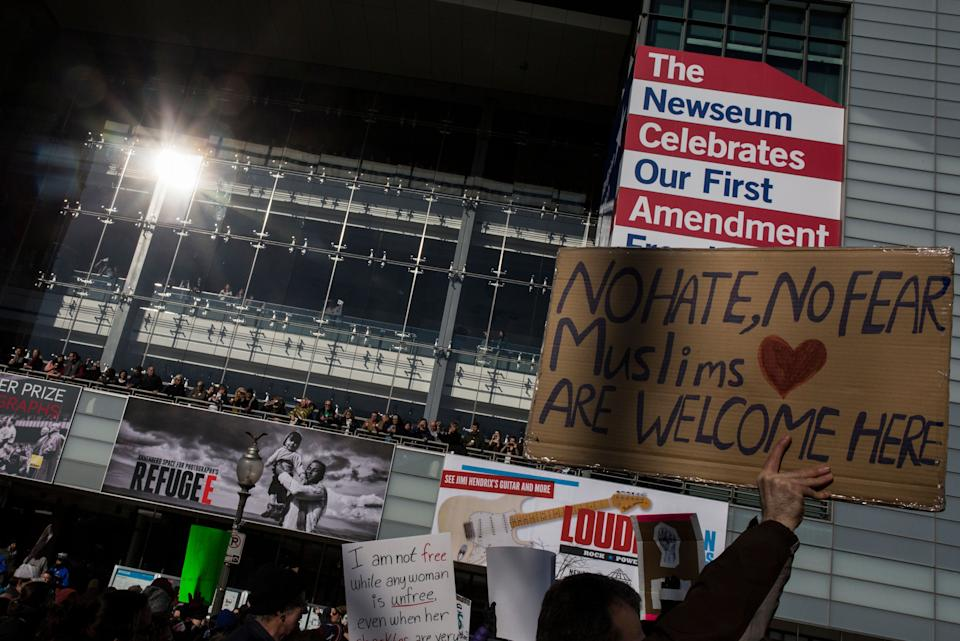 Demonstrators walk past the Newseum while marching from the White House to the Capitol Building on February 4, 2017 in Washington, DC. The demonstration was aimed at President Donald Trump's travel ban policy.