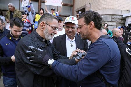 A priest congratulates and blesses Matthew Burwick, a supporter of Venezuelan opposition leader Juan Guaido, who had sat vigil outside the Venezuelan embassy for three weeks, as Guaido supporters celebrate after U.S. law enforcement officers arrested and removed the remaining activists sympathetic to embattled President Nicolas Maduro who had been part of a multi-week occupation of the embassy in Washington, U.S., May 16, 2019. REUTERS/Jonathan Ernst