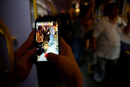 """A passenger plays the augmented reality mobile game """"Pokemon Go"""" by Nintendo inside a bus in Hong Kong, China August 12, 2016. REUTERS/Tyrone Siu"""