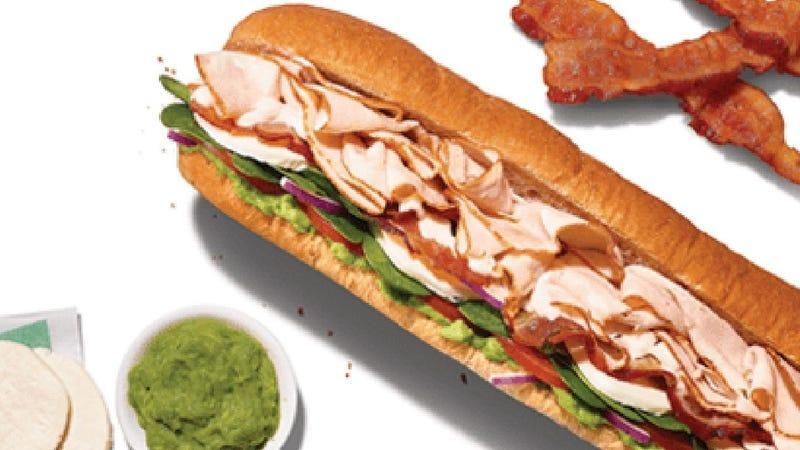 Subway's turkey cali sub with a side of green sauce and three slices of bacon on white background