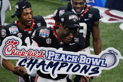 Georgia players including Georgia wide receiver George Pickens (1) celebrate victory over Cincinnati after the Peach Bowl NCAA college football game, Friday, Jan. 1, 2021, in Atlanta. Georgia won 22-21. (AP Photo/Brynn Anderson)