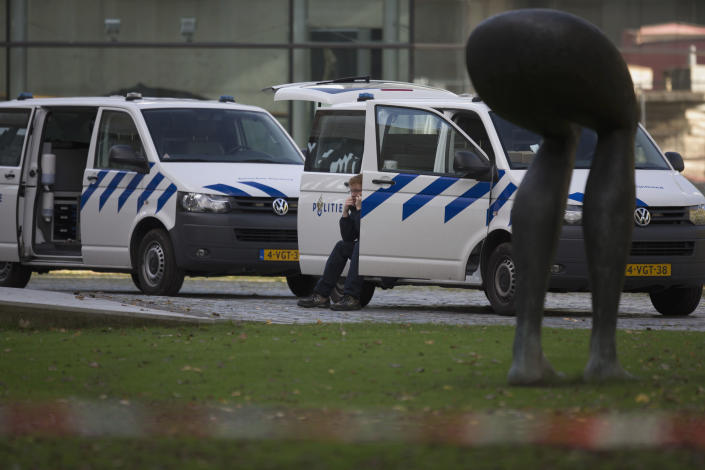 "A forensic expert talks on his mobile phone as police vehicles are parked near a statue at the back entrance of Kunsthal museum in Rotterdam, Tuesday Oct. 16, 2012. Several paintings have been stolen from a museum in the Dutch city of Rotterdam that was exhibiting works by Pablo Picasso, Henri Matisse and Vincent van Gogh. At least several paintings were stolen early Tuesday morning from the Kunsthal museum , but their names have not yet been released. They are believed to include at least one by Henri Matisse, the 1919 ""Reading Girl."" (AP Photo/Peter Dejong)"