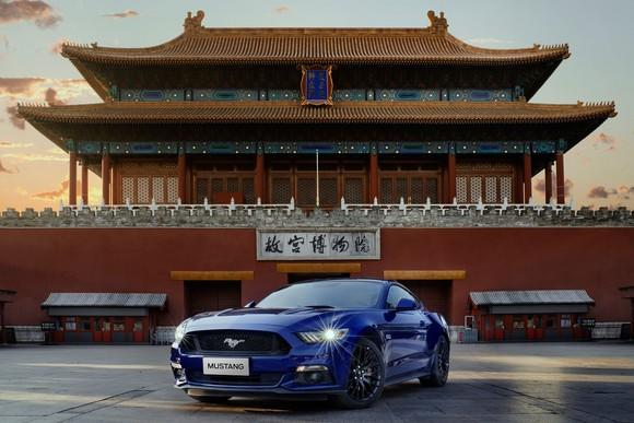 A blue Ford Mustang parked in front of a Chinese building.