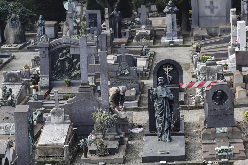 A man pays tribute to a tomb in the Monumentale cemetery, in the day devoted to remembrance of the departed, in Milan, Italy, Monday, Nov. 2, 2020. (AP Photo/Luca Bruno)
