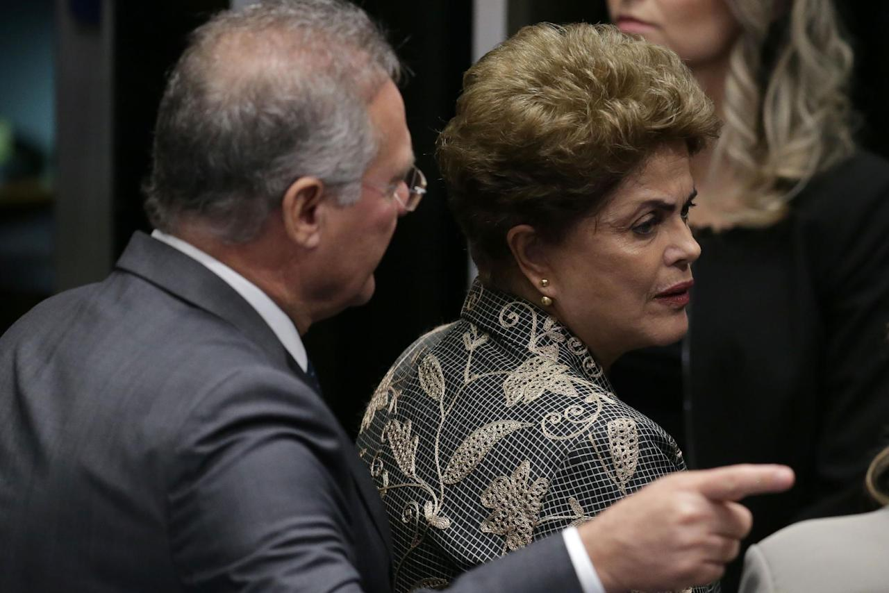 "Brazil's Senate leader Renan Calheiros points to an exit as suspended President Dilma Rousseff looks to leave Senate chambers after addressing the lawmakers, at the start of a short recess of her own impeachment trial, in Brasilia, Brazil, Monday, Aug. 29, 2016. Fighting to save her job, Rousseff told senators on Monday that the allegations against her have no merit. ""I know I will be judged, but my conscience is clear. I did not commit a crime,"" she told senators. Rousseff's address comes on the fourth day of the trial. (AP Photo/Eraldo Peres)"