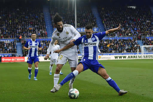 Real Madrid's Isco, left, duels for the ball with Alaves' Luis Rioja during the Spanish La Liga soccer match between Real Madrid and Alaves at Mendizorroza stadium, in Vitoria, northern Spain, Saturday, Nov. 30, 2019. (AP Photo/Alvaro Barrientos)