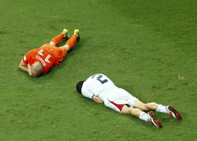 Arjen Robben of the Netherlands and Costa Rica's Johnny Acosta lie on the pitch after colliding with each other during extra time in their 2014 World Cup quarter-finals at the Fonte Nova arena in Salvador July 5, 2014. Acosta was shown yellow card for the action. REUTERS/Ruben Sprich (BRAZIL - Tags: SOCCER SPORT WORLD CUP)