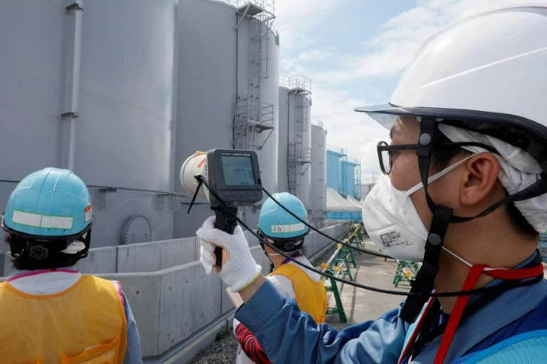 Staff measure radiation levels around the storage tanks of radiation-contaminated water at the tsunami-crippled Tokyo Electric Power Company (TEPCO) Fukushima Dai-ichi nuclear power plant in Japan