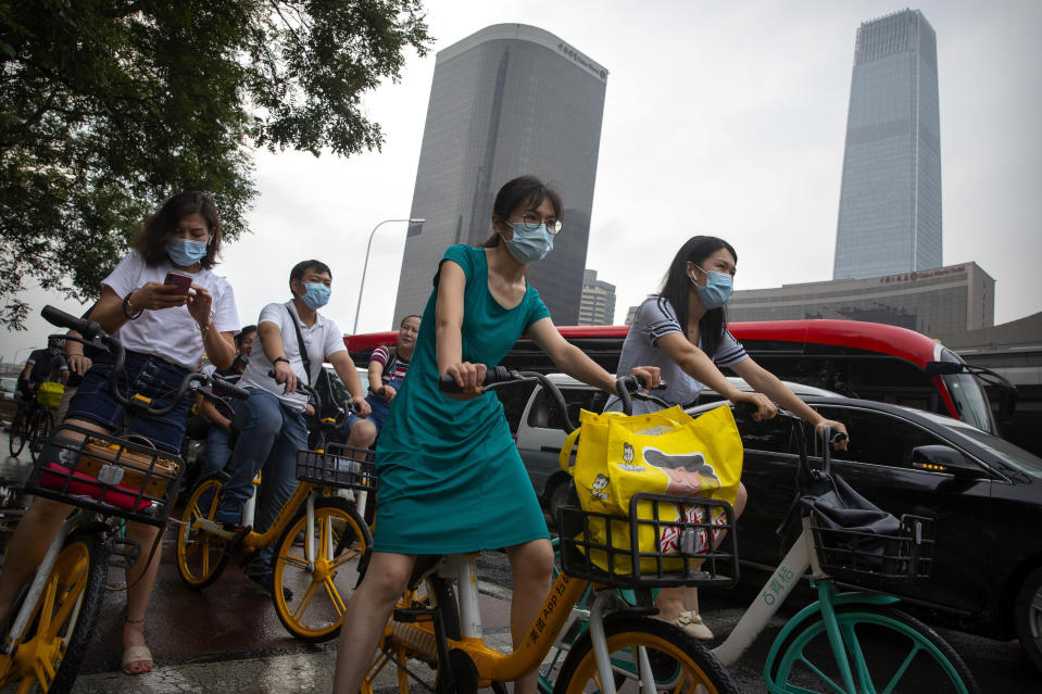People wearing face masks to protect against the coronavirus wait at an intersection in the central business district in Beijing, Friday, July 31, 2020. China is tightening travel restrictions in the capital of Xinjiang, where more than a hundred new cases were reported Friday. (AP Photo/Mark Schiefelbein)