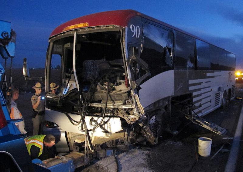 Police inspect a tour bus on the side of Interstate 10 about 50 miles south of Phoenix following a head-on collision with a pickup truck driving the wrong way on Tuesday, Nov. 20, 2012 in Casa Grande, Ariz. The driver of the pickup truck was killed. Nine people aboard the bus were injured. (AP Photo/Brian Skoloff)