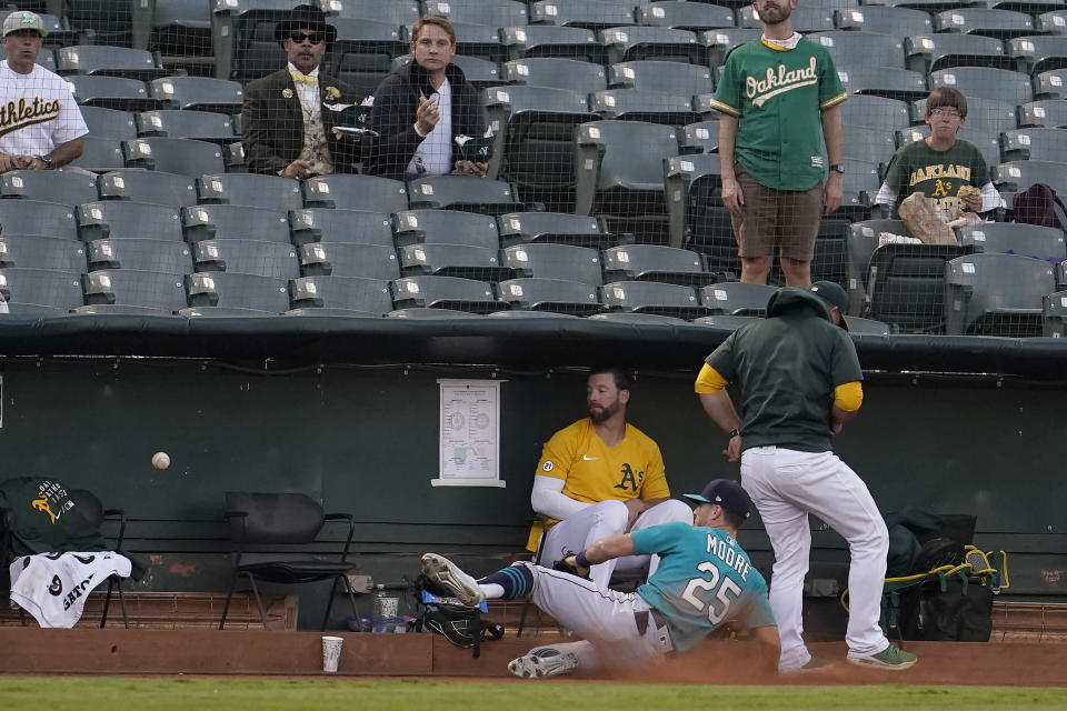 Seattle Mariners left fielder Dylan Moore (25) cannot catch a foul ball hit by Oakland Athletics' Matt Olson as he slides into the Athletics bullpen during the first inning of a baseball game in Oakland, Calif., Monday, Sept. 20, 2021. (AP Photo/Jeff Chiu)
