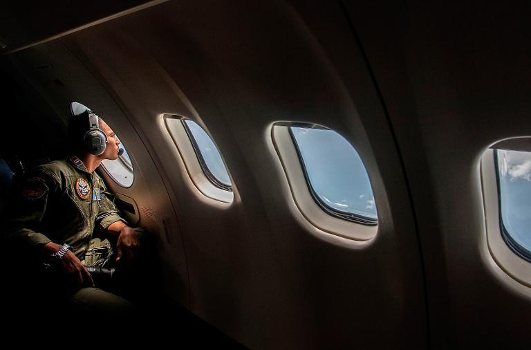 A member of the Indonesian military looks out of the window during the search for missing AirAsia flight QZ8501, over the waters of the Java Sea on December 29, 2014