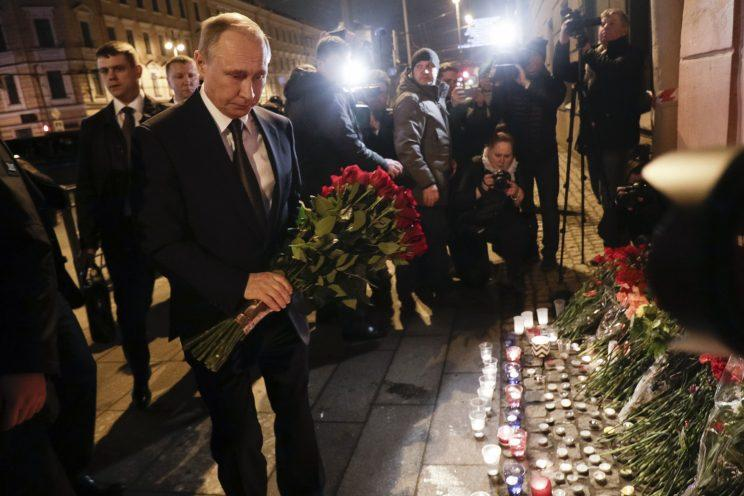 Vladimir Putin leaves flowers after the St Petersburg metro attack